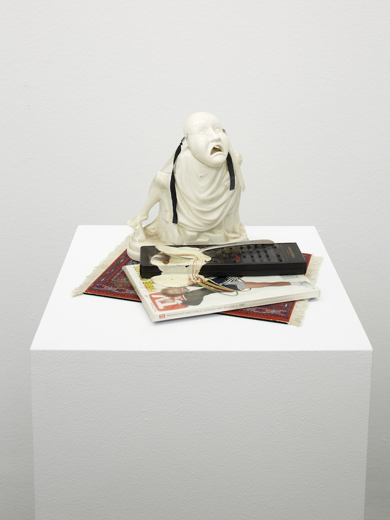 Danny McDonald, <i>Tragic Relativity</i>, 2015, ceramic lacquer, Pieta, ceramic tragedy mask, TV remote control, spoon with imitation icecream, 1993 TV guide (Richard Simmons cover), miniature carpet, 20 x 27 x 27 cm
