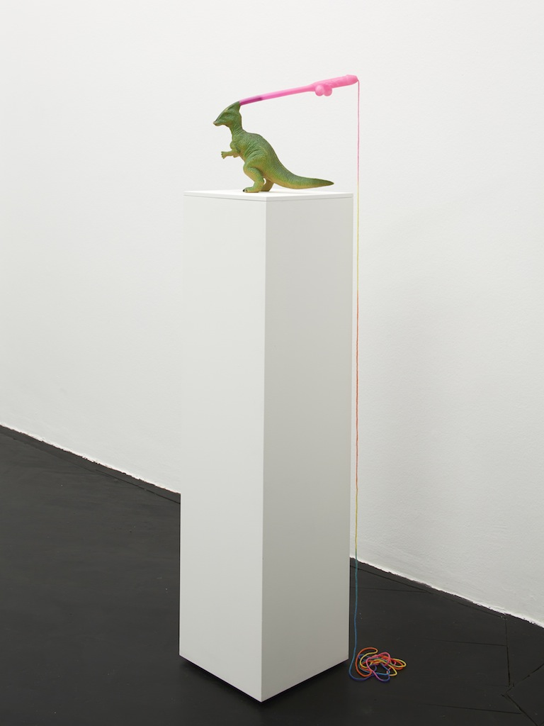 Danny McDonald, <i>The Last of his Kind at The End of The Line</i>, 2015, plastic dinosaur, novelty straw, rainbow yarn, 22 x 27 x 27 cm