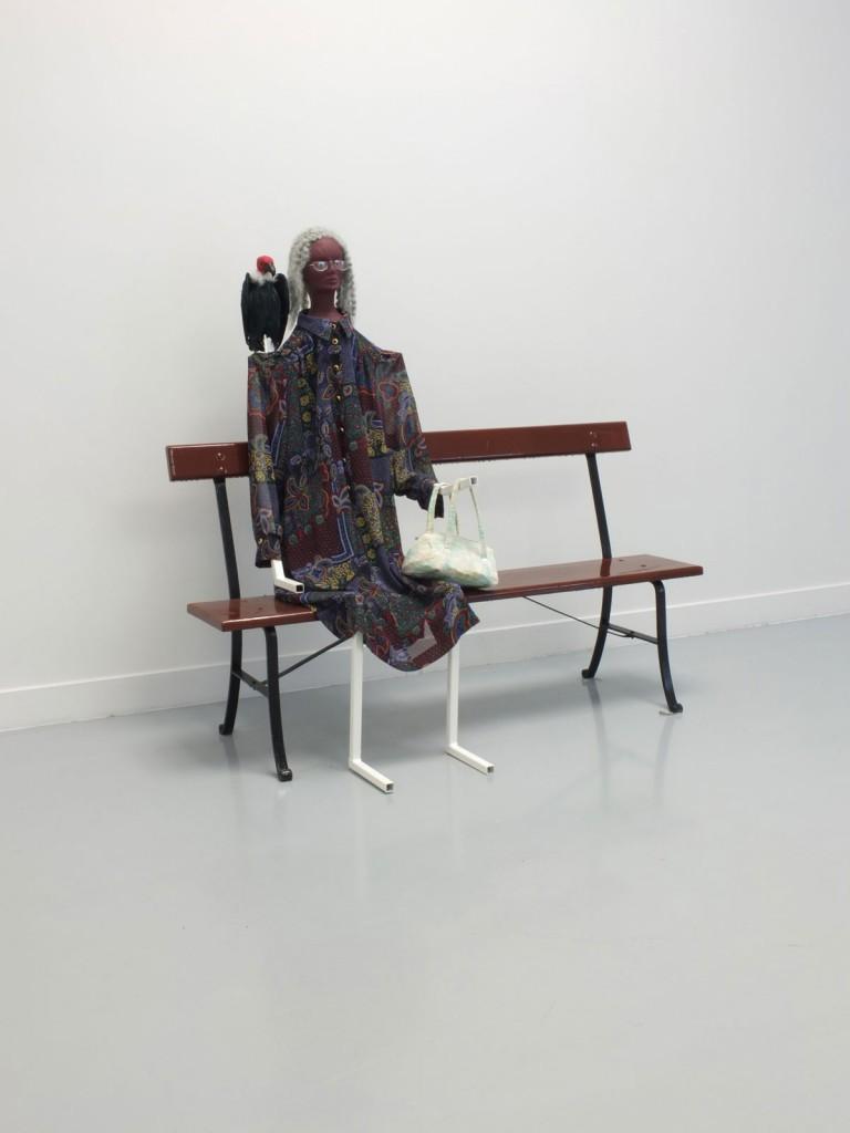 Jos de Gruyter & Harald Thys. »Hildegard«. 2013. metal skeleton painted white, styrofoam head, dress, handbag, fake bird, wooden brown painted bench with metal structure. 150 x 160 x 80 cm. Unique