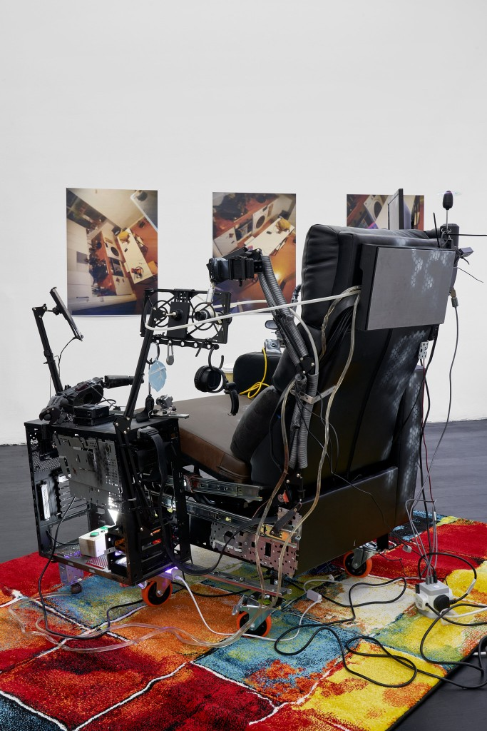 Chris, 2021<br> Installation, dimensions variable<br> Monitor with video-loop (2:27 minutes), broken monitor, multiple broken  computer parts, uv lights, usb uv light,  2 usb fans, standard light, wheels, cinema chair, drawer runners, broken cameras,  cables and cable ties and bolts, plastic  tubing, ready-made rug (160 x 230 cm),  8 Polly Pocket posters (59,4 x 84 cm each). Photos: Graysc.